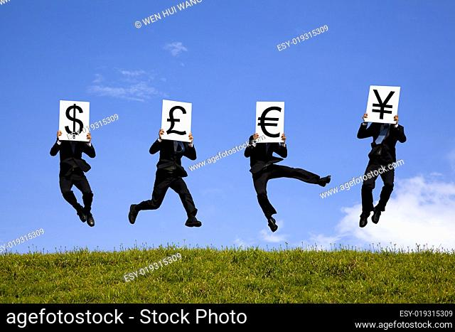 businessman jumping and holding 4 different currency signs. dollar, pond, euro