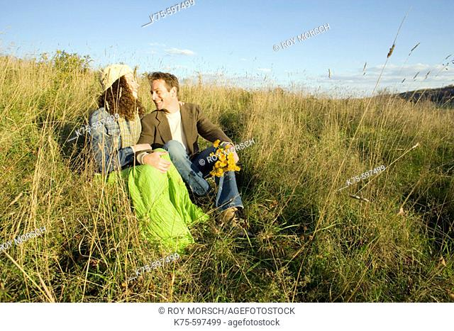 Couple together on hilltop in field