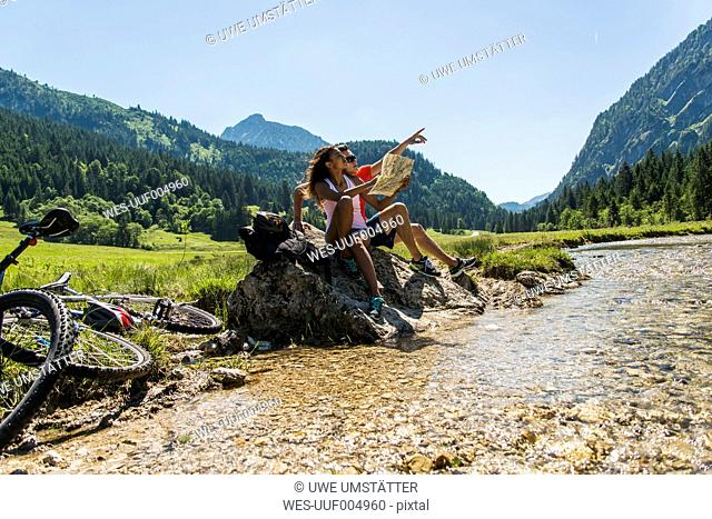 Austria, Tyrol, Tannheim Valley, young couple with mountain bikes and map sitting at brook