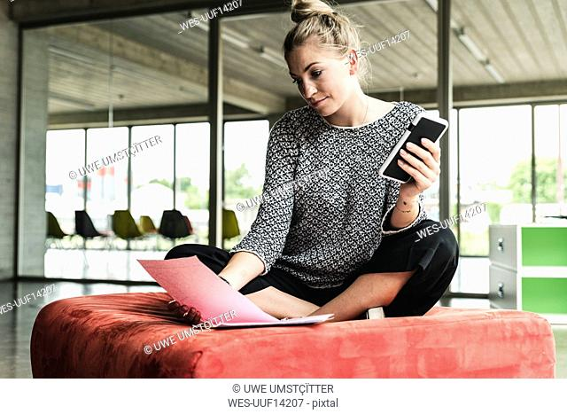 young businesswoman working in modern office, sitting on stool, reading documents