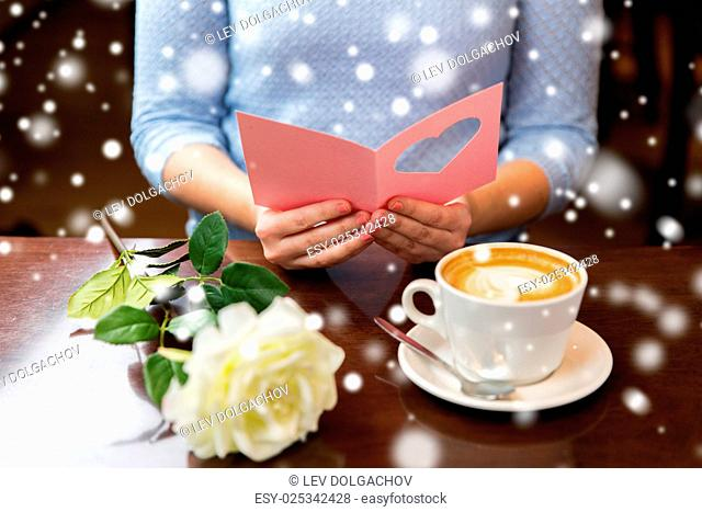 holidays, valentines day, people and love concept - woman reading greeting card with heart, flower and coffee cup over snow