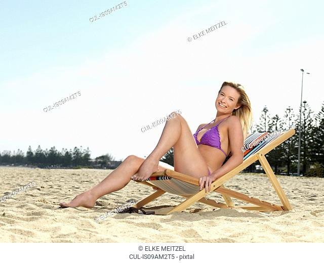 Portrait of young woman posing on deck chair at beach, Altona, Melbourne, Victoria, Australia