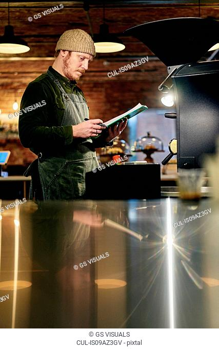 Male coffee shop owner at coffee roaster with clipboard