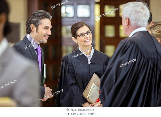 Judges and lawyers talking outside courtroom
