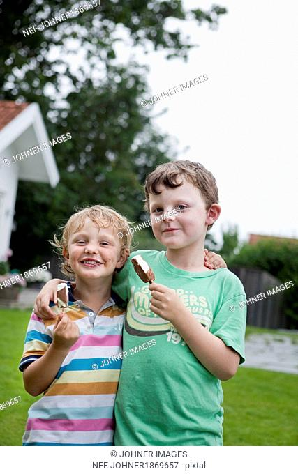 Brothers holding ice cream and looking at camera