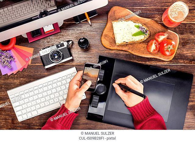 Overhead view of male hands editing photographs from smartphone on graphic design tablet using digital pen
