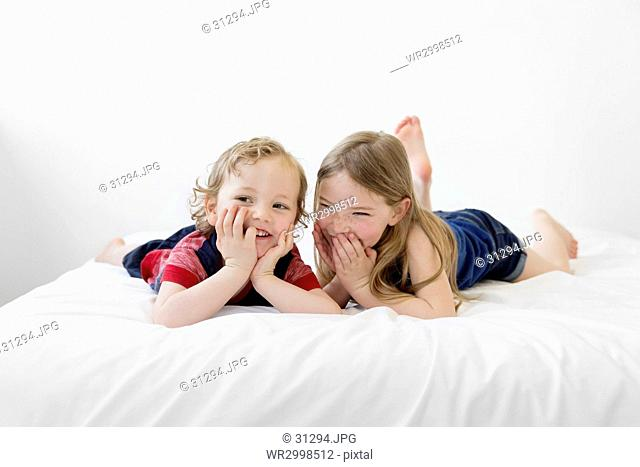 A six year old girl and four year old boy, brother and sister lying on a bed looking at the camera