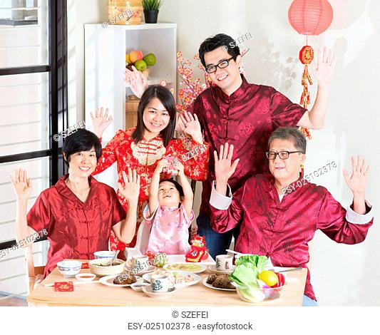 Chinese New Year, reunion dinner. Happy Asian Chinese multi generation family with red cheongsam dining at home
