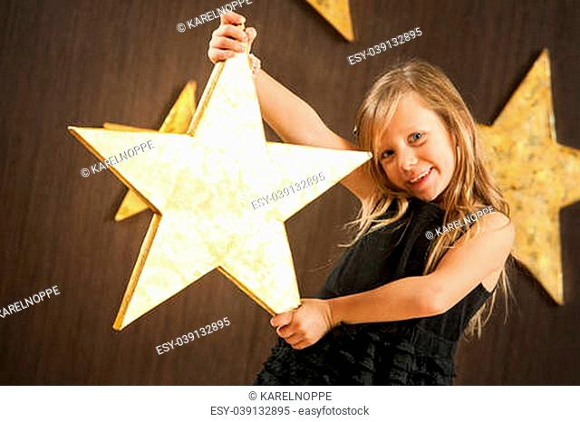 Portrait of cute girl holding big golden star