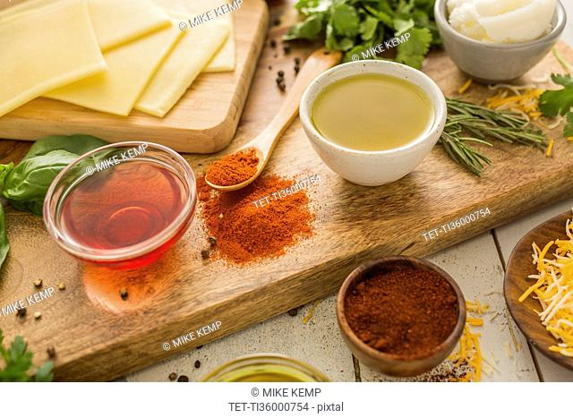 Spices, olive oil, vinegar and cheese on cutting board