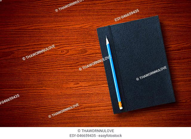 Top view of pen with black leather notebook put on brown wooden tabletop background