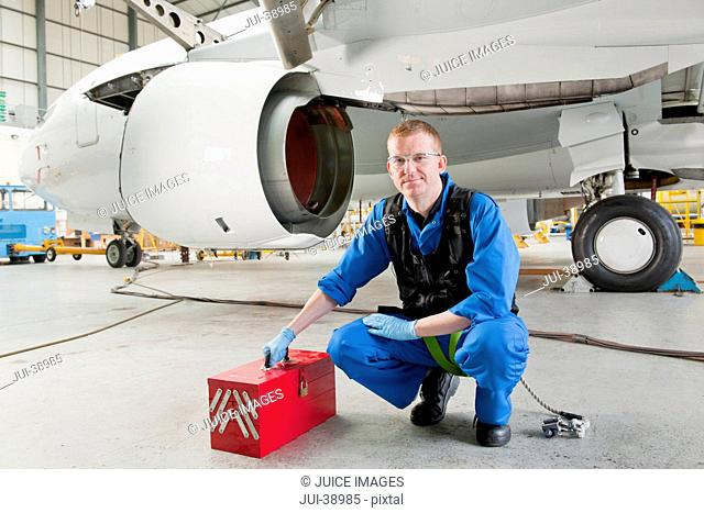 Portrait of engineer with tool box near passenger jet in hangar