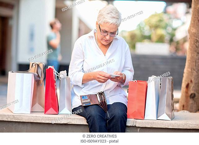 Mature woman shopper sitting on wall reading smartphone texts