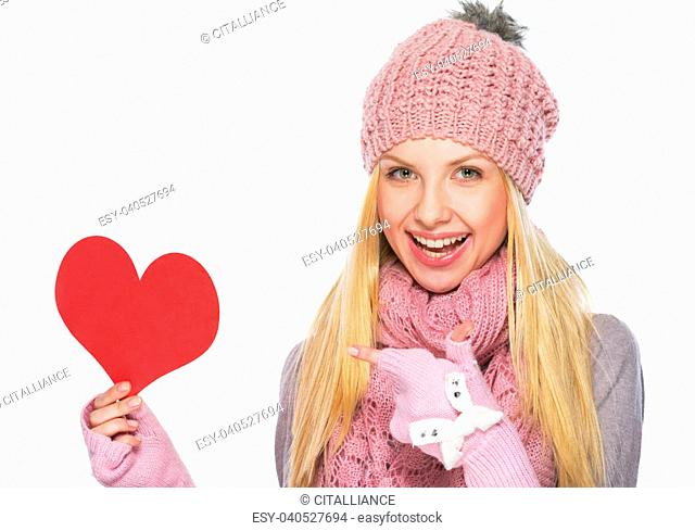 Happy teenager girl in winter hat and scarf pointing on heart shaped postcard