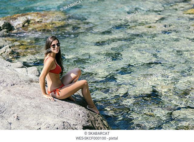 Woman wearing a red bikini sitting on stone, smiling