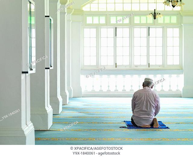 An elder man praying in a mosque
