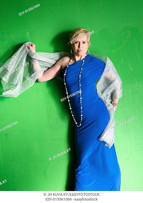 Mature woman wearing blue dress and posing, green concrete wall on background