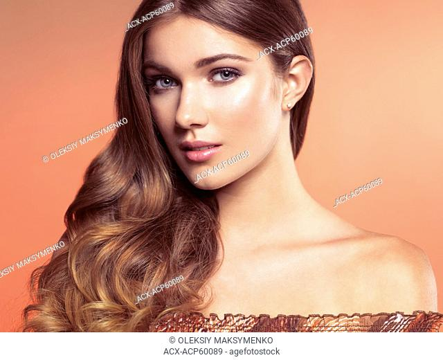 Beauty portrait of a young beautiful woman with natural look and long wavy brown hair on beige background