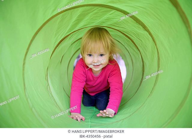 Little girl with pink shirt crawling through green playing tunnel, Germany