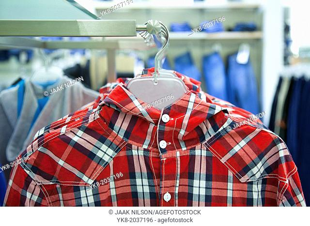 Close-up of blouse, shirt on hanger. Rack, colorful clothing. Fashion in retail store, shop