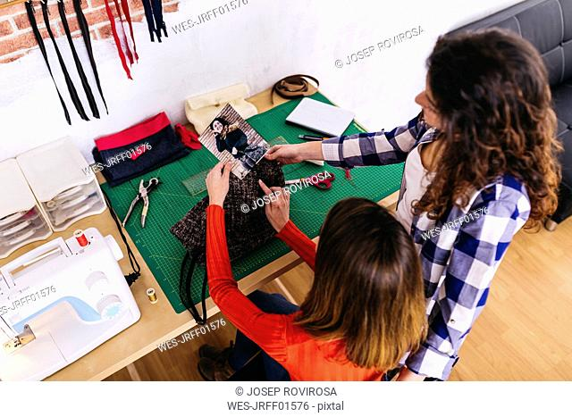 Two fashion designers in studio looking at photography