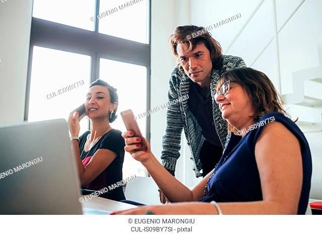 Businesswomen using smartphone and working in loft office