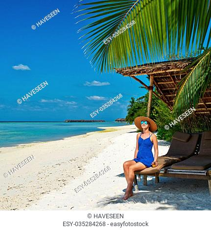 Woman in blue dress on a tropical beach at Maldives