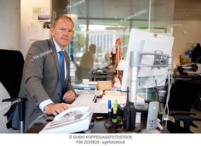 Klosterstrasse, East-Berlin, Berlin, Germany. Senior adult male facility manager, working at his desk, supporting the staff of the Dutch embassy