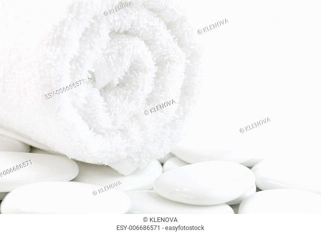 White pebbles and towel over white. Selective focus