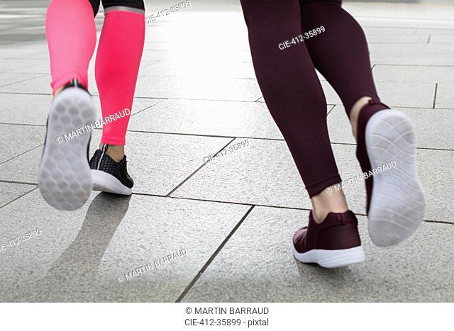 Close up feet of female runners jogging