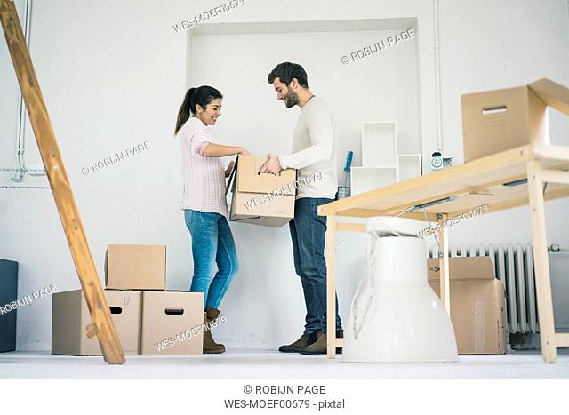 Couple moving into new home unpacking cardboard boxes