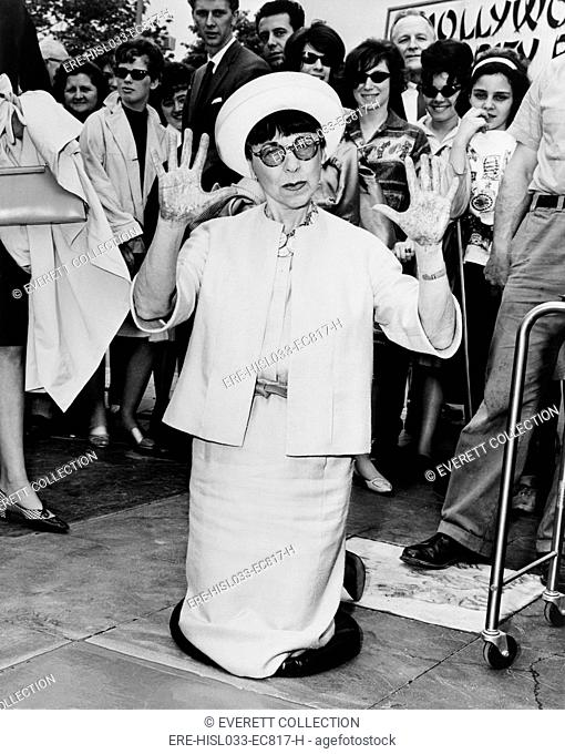 Edith Head, leaving hand prints in cement outside the Hollywood Pavilion in 1964. She won eight Academy Awards for her movie costume design