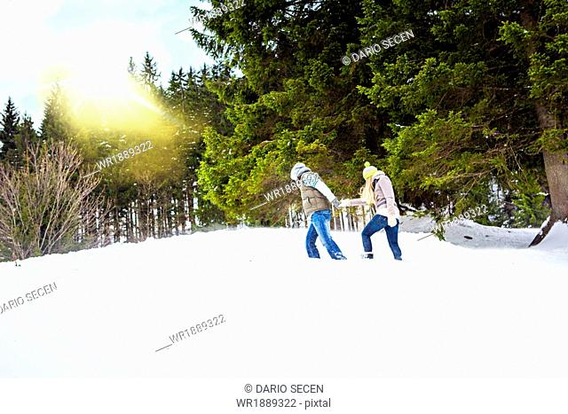 Couple Walking In Snow, Spitzingsee, Bavaria, Germany