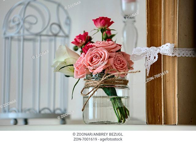 Bouquets of roses on a shelf with old books and a beautiful decorative white cell