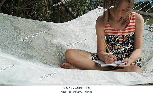 girl in a hammock writing