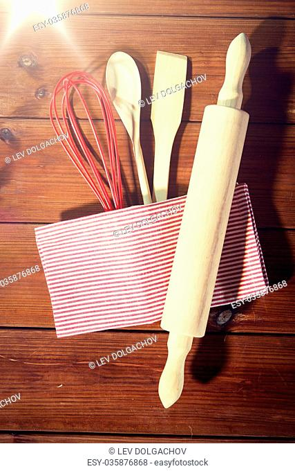 baking, cooking and home kitchen concept - close up of kitchenware set on wooden board from top