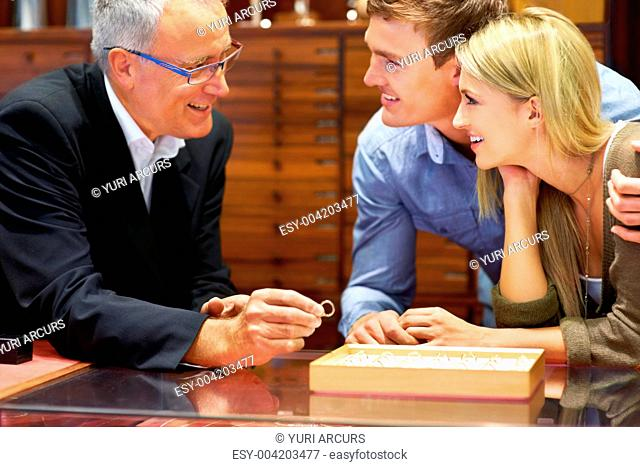 Professional jeweller helping an attractive young couple to choose an engagement ring