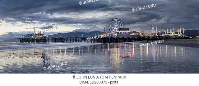 Funfair on Santa Monica pier reflecting in water, Santa Monica, California, USA