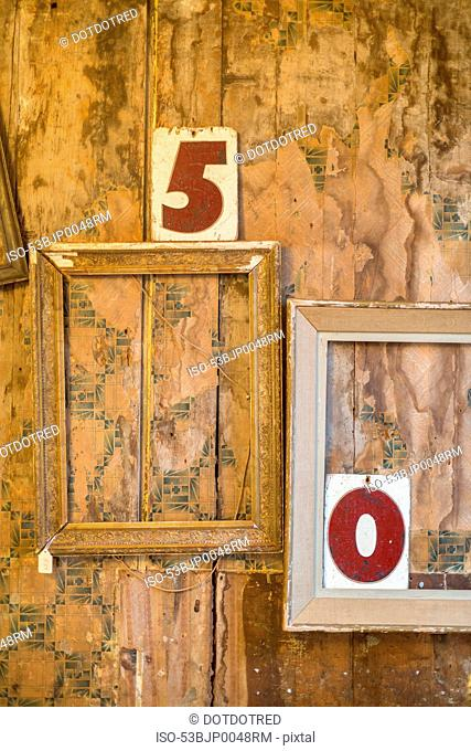 Empty picture frames and numbers on wall