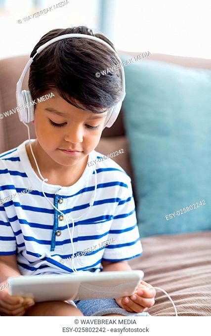 Boy listening music on digital tablet in living room
