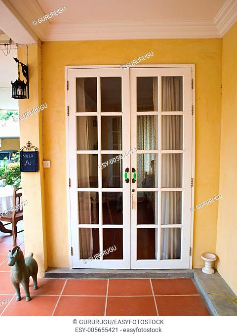 Double patio white french doors with windows on yellow wall