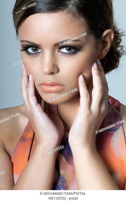 Beautiful young woman hands touching face