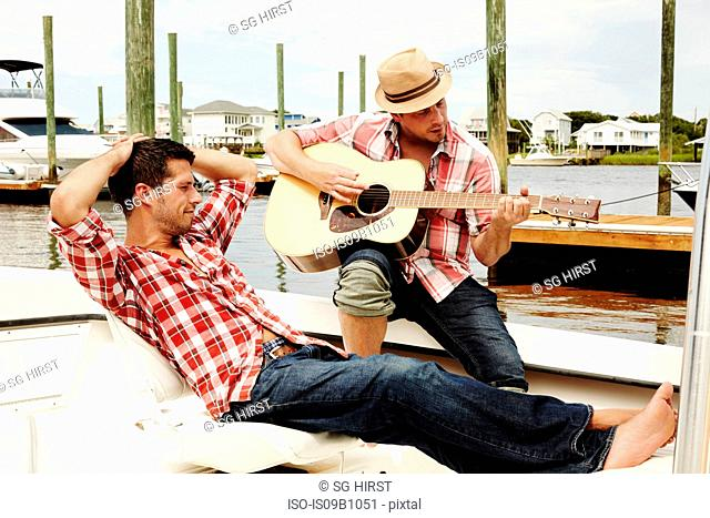 Two adult brothers relaxing playing acoustic guitar on marina motorboat