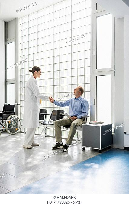 Doctor greeting, shaking hands with patient in clinic waiting room