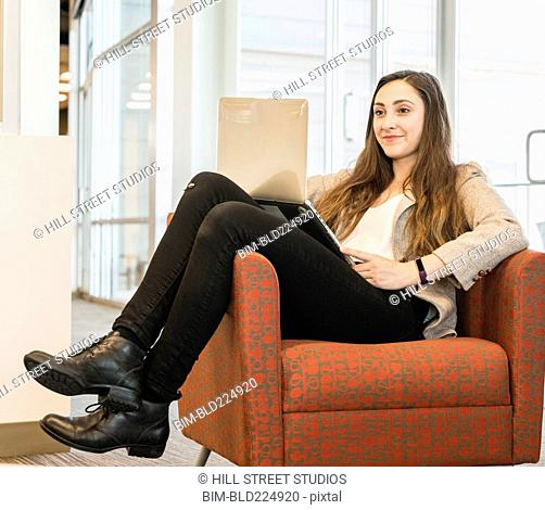 Businesswoman with feet up in armchair using laptop