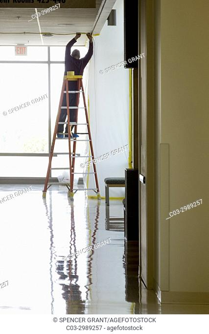 Silhouetted against a bright window, a Hispanic workman on a ladder repairs a hallway ceiling in an Irvine, CA, hospital