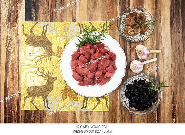 Plate of raw goulash, dried figs, plum and garlic bulbs on wooden background