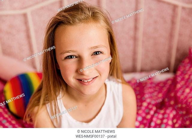 Portrait of smiling little girl in bedroom