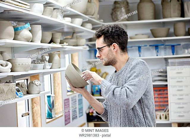 A man inspecting a clay pot, before firing. Shelves in a pottery studio full of pots, work in progress