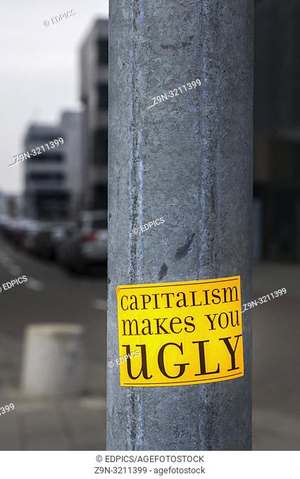 """sticker on a lamp post in financial district with a text that reads: """"""""capitalism makes you ugly"""""""""""
